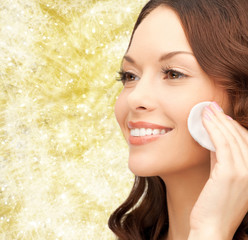 smiling woman cleaning face skin with cotton pad