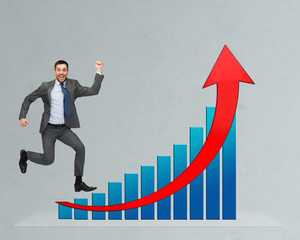 happy businessman jumping over growth chart