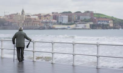 anciano con paraguas paseando por la ciudad