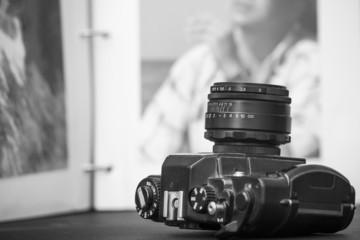 Old SLR camera on opened photo album background