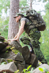 young soldier with backpack in forest
