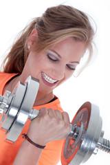 Junge sportliche Frau macht Hantel Training und lacht