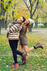 Two beautiful girlfriends having fun in the park on colorful aut