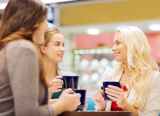 smiling young women with cups in mall or cafe