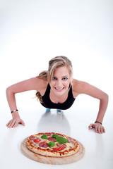 Erst Sport und dann Pizza essen. Frau macht Liegestützen