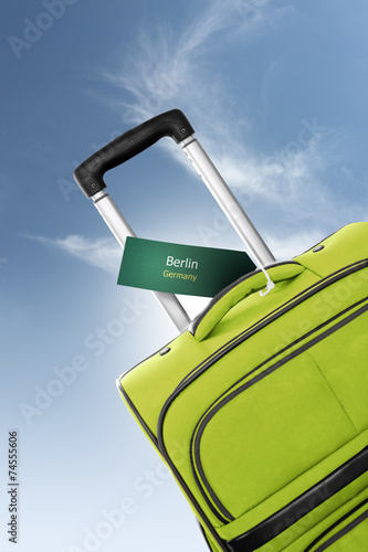 canvas print picture Berlin, Germany. Green suitcase with label