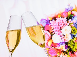 champagne flutes on wedding flowers background