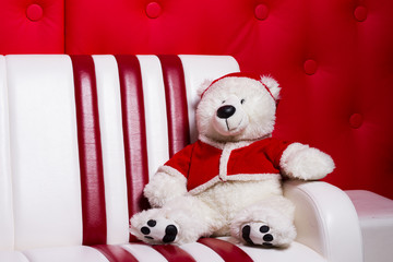 Christmas bear on the couch with a cap of Santa Claus