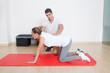 Physiotherapeut zeigt Patientin eine Dehnübung
