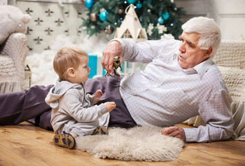 Toddler boy and grandpa playing with toy dinosaur at Christmas