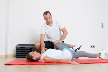 Senior woman stretching with physiotherapist