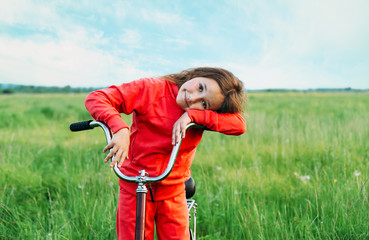 Cute little girl standing with a bicycle in summer