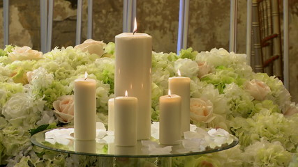 Close-up of lighted candles on flowers background