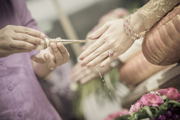 hand of a bride and groom receiving holy water