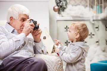 Senior man taking photo of his grandson at Christmas time