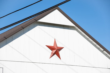 Red Mennonite star on end of white building