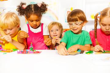 Group of kids in kindergarten play with plasticine