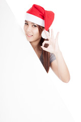 Asian girl with red santa hat show OK with oblique blank sign