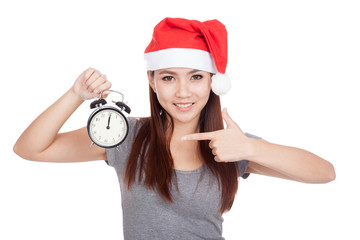 Asian girl with red santa hat point to alarm clock