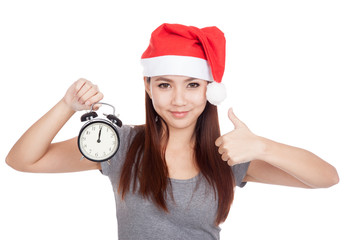 Asian girl with red santa hat thumbs up with alarm clock