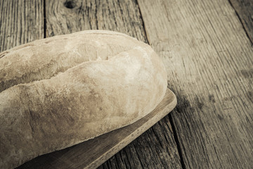 Bread on a Bread Board with Rustic Wood Background