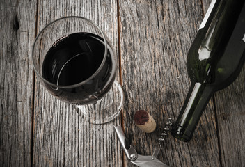 Green Wine Bottle and Cork with Red Wine and corkscrew