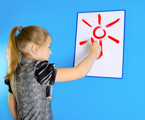 the girl draws the sun on a white plastic board