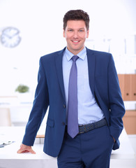 Business man or manager standing against his desk at office with