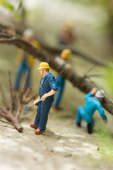 Miniature workers clearing fallen trees