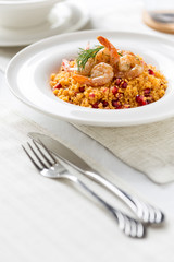 couscous with prepared shrimps and dill in white plate
