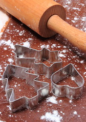 Cookie cutters and rolling pin on dough for gingerbread