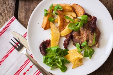 Slices of roasted pork meat with dried potatoes and lettuce