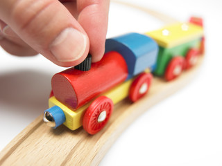 Colorful wooden toy train with hand isolated on white