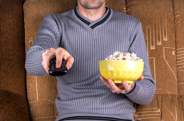 Man with remote control and popcorn