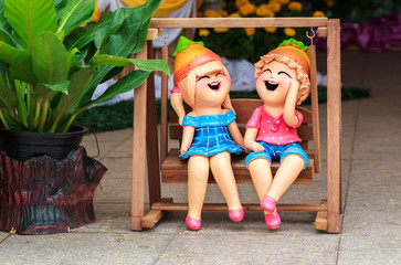 Boy and Girl Clay dolls in Wooden swings