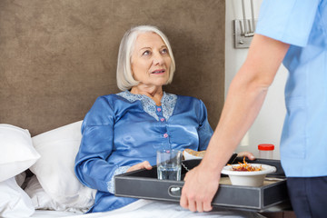 Midsection Of Nurse Serving Breakfast To Senior Woman