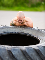 Male Athlete Lifting Truck Tire