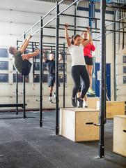 Athletes Exercising On Gymnastic Bars
