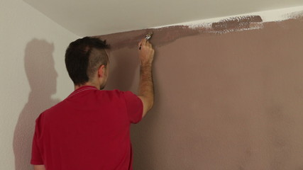 Man with a paint brush decorating interior.