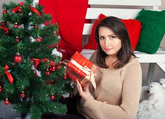 Happy pretty woman holds Christmas present near  fir tree