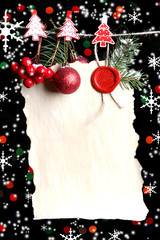 Blank sheet with Christmas decor on black background with