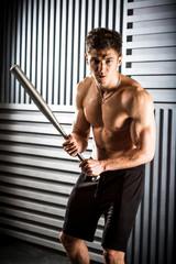 muscular man posing with a bat