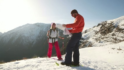 Couple hikers checking map from mountain peak