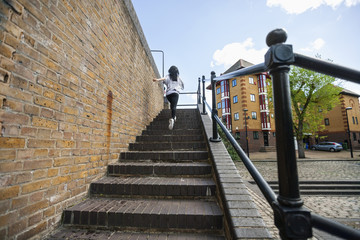 Full length rear view of young woman walking up stairs outdoors