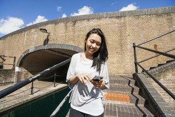 Smiling young woman using smart phone on stairs