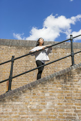Low angle view of young woman looking away while leaning on railing against cloudy sky
