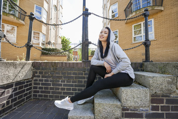 Full length portrait of young woman sitting on stairs against building