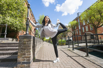 Full length of young fit woman exercising on sidewalk