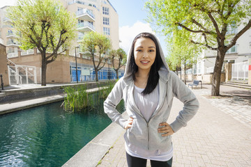 Portrait of beautiful fit woman standing by canal against buildings