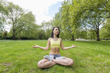 Full length of beautiful fit woman performing yoga at park